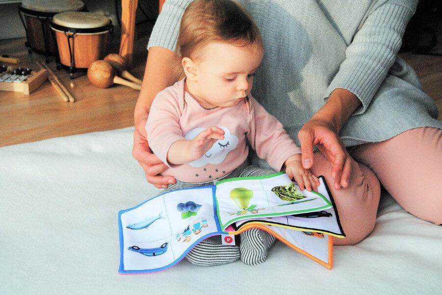 Czytanie dziecom - maluszek ogląda książkę z obrazkami